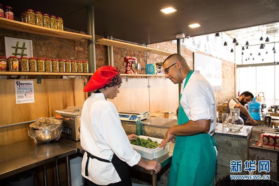 El chef ejecutivo del día habla con un alumno cuando prepara la cena