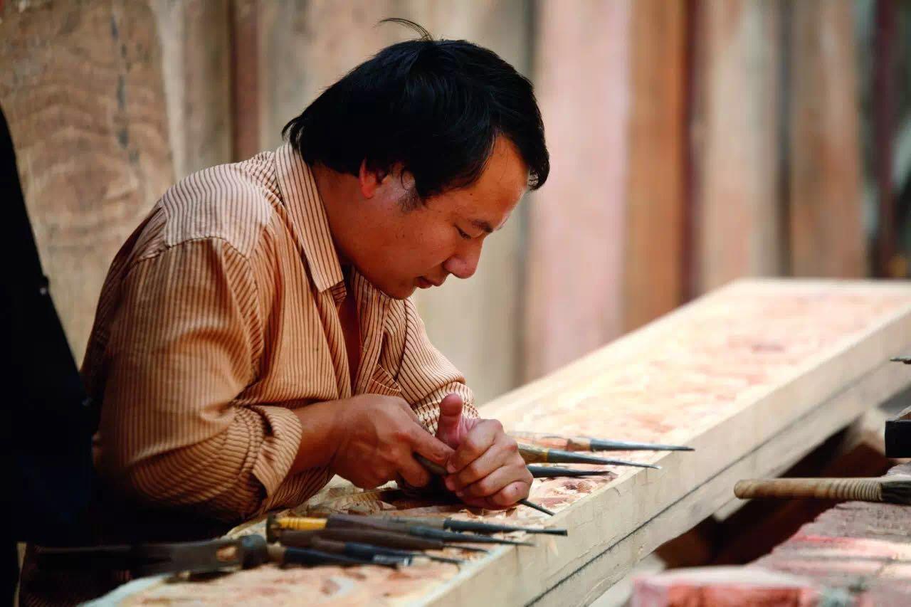 """在云南各个古镇内都有着雕刻得活灵活现的木窗和木门,它们大多来自大名鼎鼎的剑川。剑川的木雕起初多服务于白族建筑,因为手艺精湛而广为流传。在北京的故宫、天坛、圆明园、颐和园都有剑川木雕的身影。常见的剑川木雕要属""""格子门"""",一缕阳光穿过,精细的镂空窗花把阳光切割成不同的形状倒映在地板上,发出细碎的光芒。剑川的沙溪古镇目前依然有一些手工艺人经营的工作坊进行现场雕刻,你可以亲眼目睹这些方寸之间的高超技艺。"""