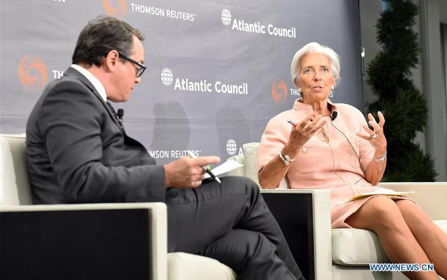 International Monetary Fund (IMF) Managing Director Christine Lagarde (R) speaks on