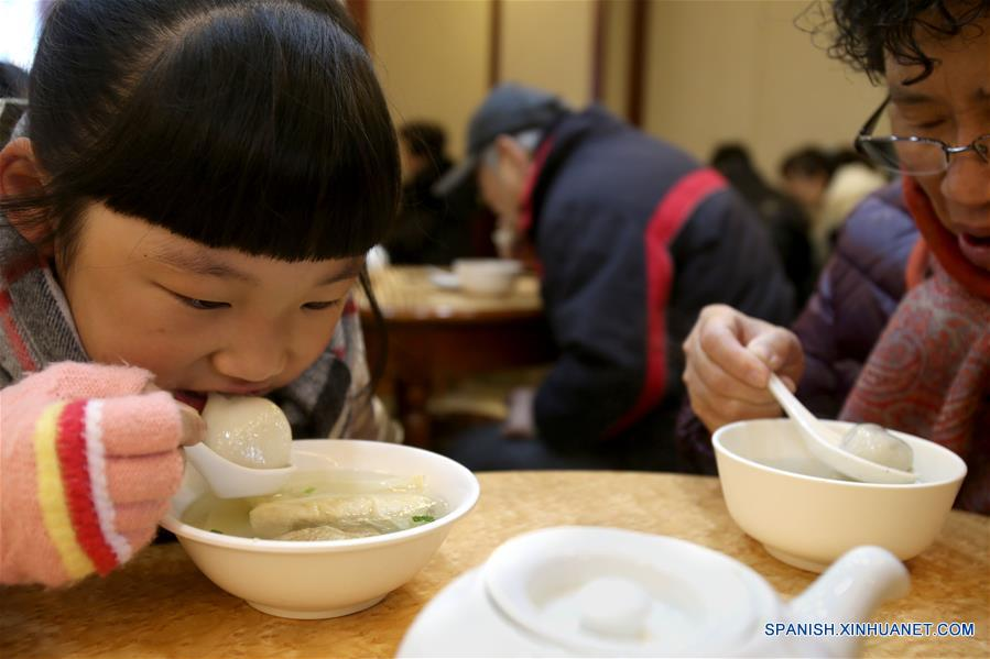 """SHANGHAI, febrero 9, 2017 (Xinhua) -- Personas comen Tangyuan, pequeñas bolas de masa hervida elaboradas de harina de arroz glutinoso y relleno de dulce, en una famosa tienda nombrada """"Ningbo Dumplings"""", en Shanghai, en el este de China, el 9 de febrero de 2017. Como tradición, los residentes chinos comen Tangyuan para celebrar el Festival de Linternas en el quinceavo día del Año Nuevo Lunar chino, que este año se conmemora el 11 de febrero. Cerca de 70,000 bocadillos dulces han sido vendidas por día por esta tienda durante los días recientes. (Xinhua/Liu Ying)"""