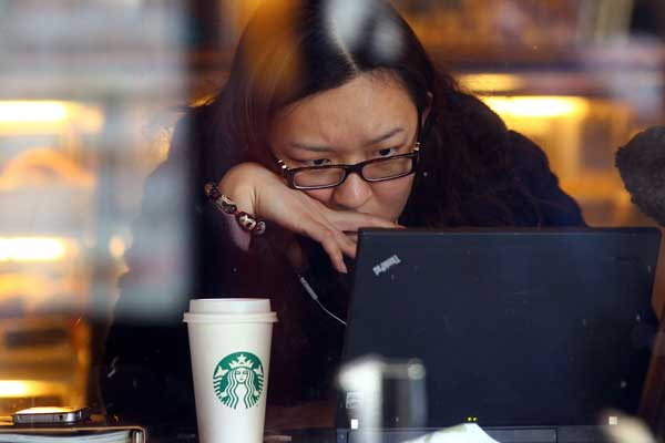 A woman surfs internet at a Starbucks outlet in Beijing. [Photo by Zou Hong/China Daily]