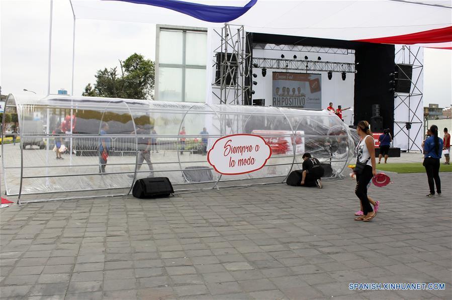 """Una mujer camina frente a un preservativo gigante durante el I Festival Informativo """"Condón Fest"""" en el marco del Día Internacional del Condón, organizado por la AHF Perú, filial de AIDS Healthcare Foundation, en la ciudad de Lima, Perú, el 11 de febrero de 2017. Bajo el lema """"¡Los Condones Siempre de Moda!"""" se realizó el sábado en Lima el I Festival Informativo """"Condón Fest"""", con el fin de hacer un llamado a los jóvenes sobre el uso responsable del condón para prevenir infecciones de transmisión sexual, así como los embarazos no deseados. AHF Perú distribuirá 70 mil preservativos gratuitos en Lima, Ica, Loreto y Lambayeque, como parte de su trabajo de sensibilización y prevención, de acuerdo con información de la prensa local. (Xinhua/Luis Camacho)"""