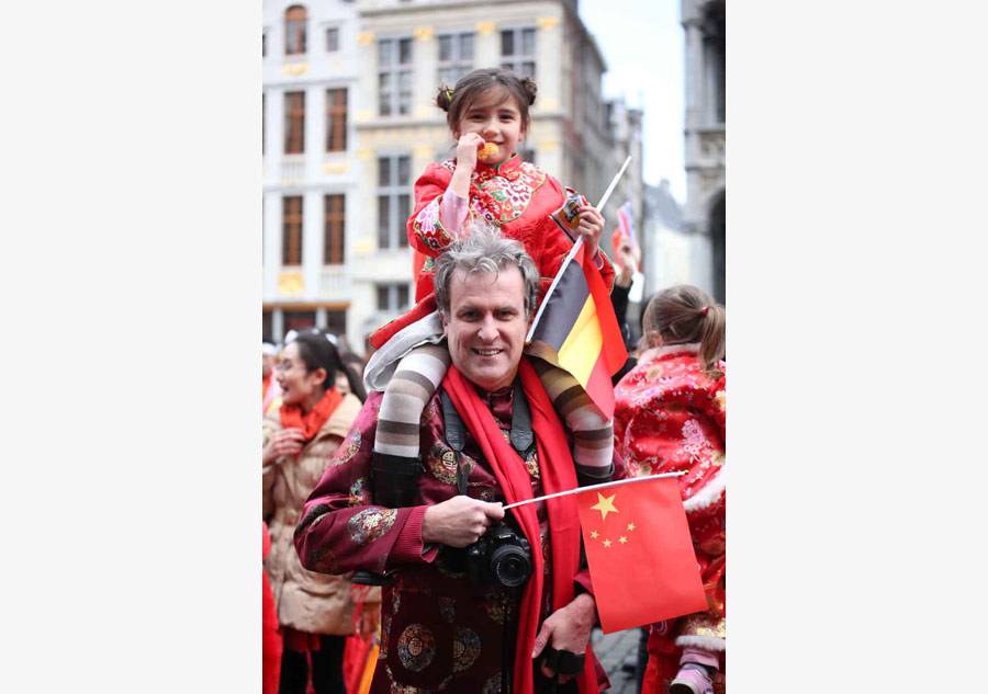 A Belgian man and his daughter wear Tangzhuang, a traditional Chinese suit featuring typical Chinese embroidery, at a Chinese New Year celebration event. [Photo by Zhang Miaojing]