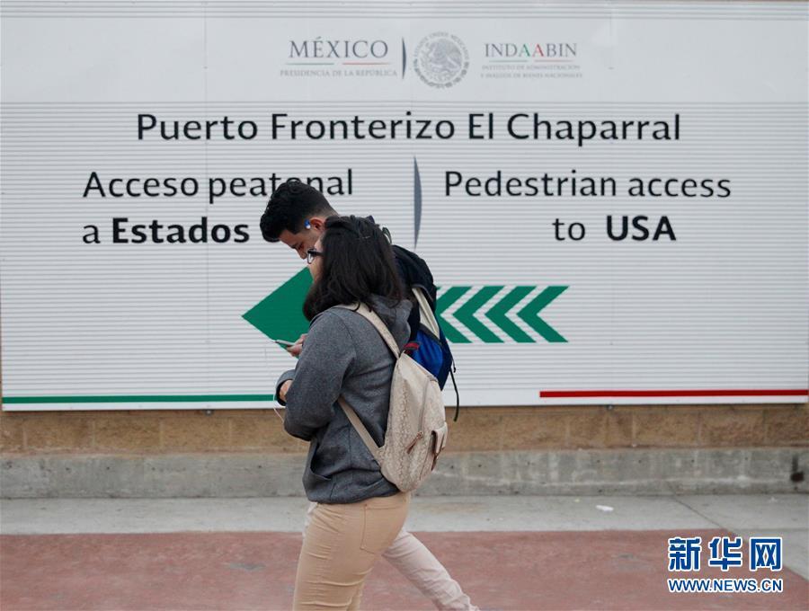 Jaime y su compañero pasan por una tabla de anuncio que se alza en el acceso peatonal a Estados Unidos