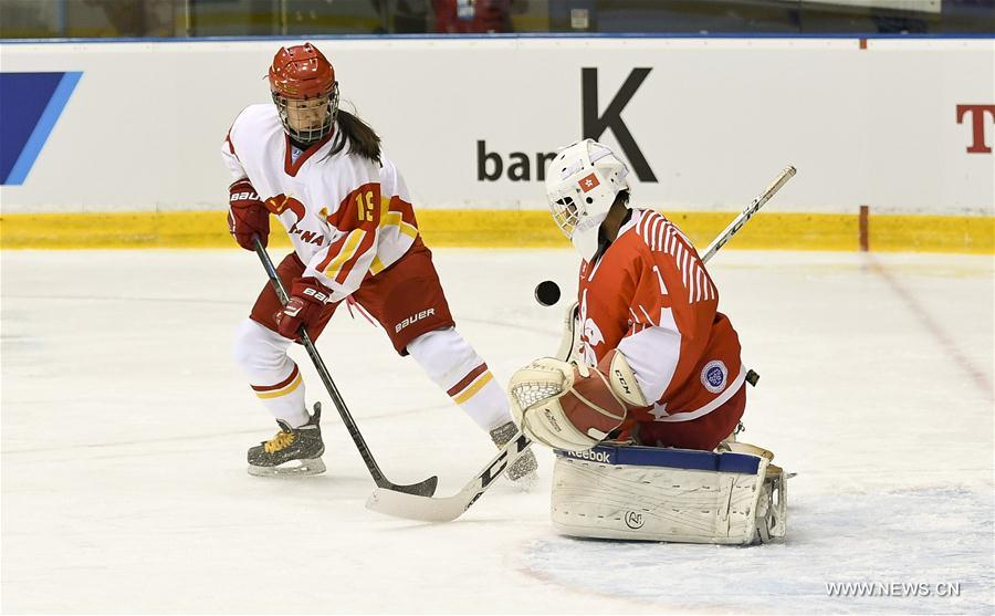 He Xin (L) of China takes a shot during the women