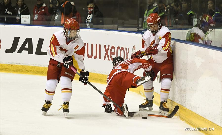 Kong Minghui(R) and Zhang Mengying (L) vie for the puck during the women