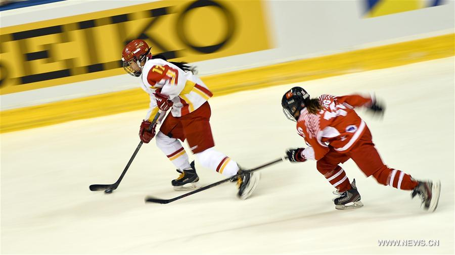 Lyu Yue (L) of China vies for the puck during the women