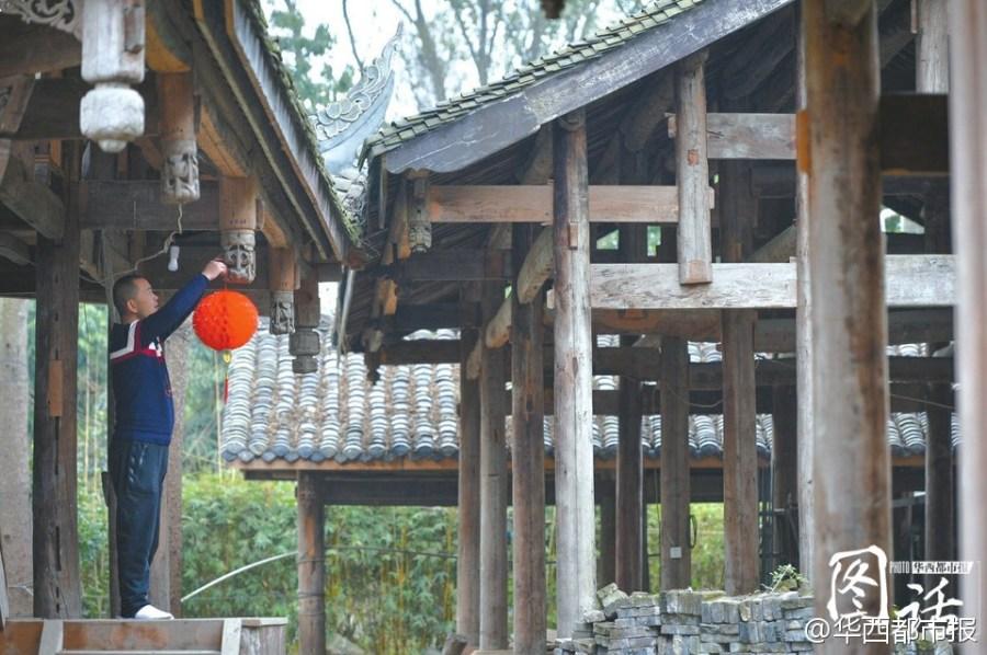 En el Inicio de la Primavera, Li Xiaochun cuelga un farol rojo a una casa antigua y espera que pueda tocar el zheng cantando bajo el techo para experienciar la vida de los antepasados en el futuro