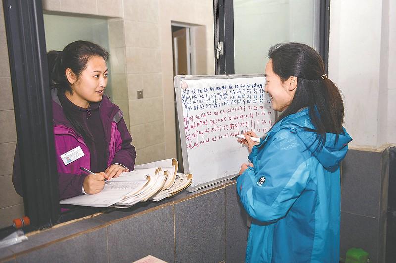 饲养员仔细记录下每一只幼年大熊猫的体重。
