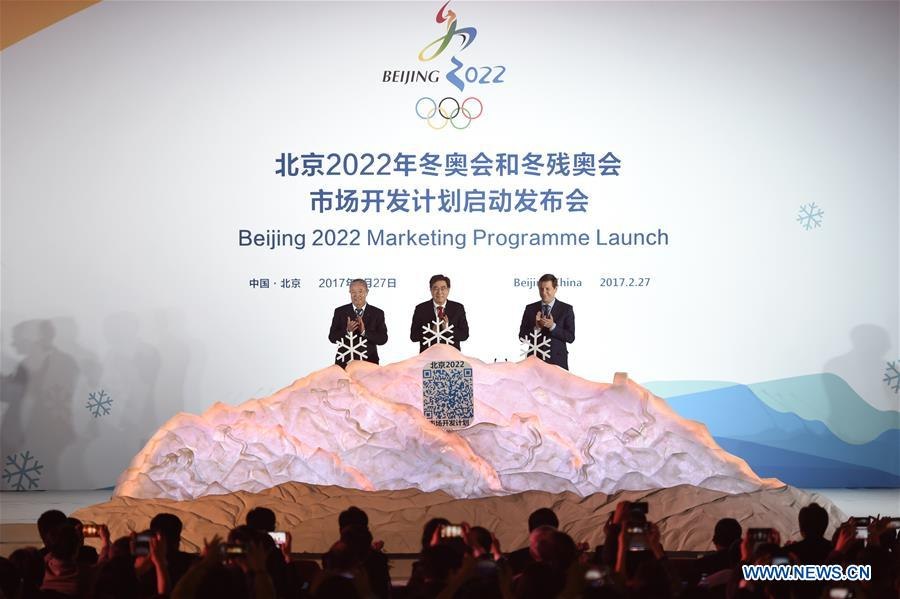 Beijing 2022 President Guo Jinlong (C), International Olympic Committee (IOC) Vice President Yu Zaiqing(L) and IOC Coordination Commission Chairman Alexander Zhukov clap after they put the white snowflake into a model of snow mountain to unlock the marketing program of Beijing 2022 Olympic and Paralympic Winter Games (Beijing 2022) in Beijing, capital of China, Feb. 27, 2017. The marketing program for Beijing 2022 was officially launched by the organizers here on Monday. (Xinhua/Ju Huanzong)