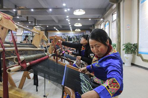 武陵源区乖幺妹织锦有限公司内,员工正在木腰机前忙碌。