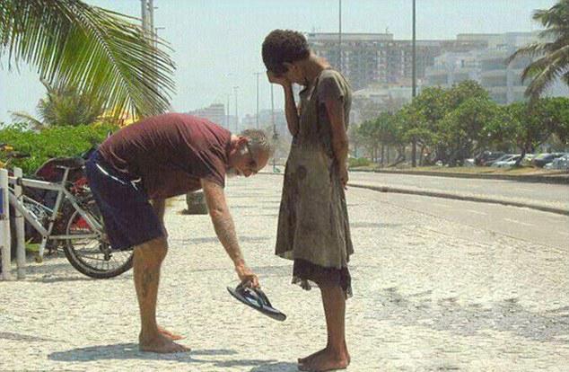 巴西里约热内卢海滩上的一名男子将自己的拖鞋赠给了一名无家可归的光脚女孩。