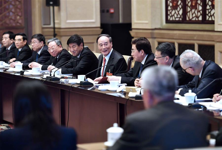 Wang Qishan, a member of the Standing Committee of the Political Bureau of the Communist Party of China (CPC) Central Committee, joins a panel discussion with deputies to the 12th National People