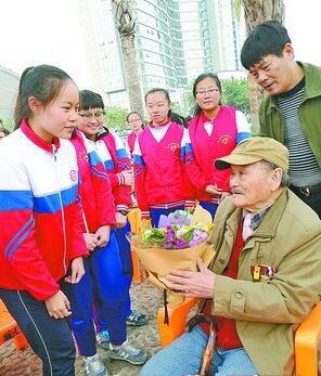■钟庆达(穿绿色上衣者)带学生慰问老兵。
