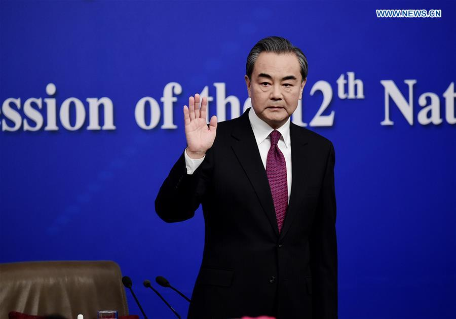 Chinese Foreign Minister Wang Yi waves to media at a press conference on China