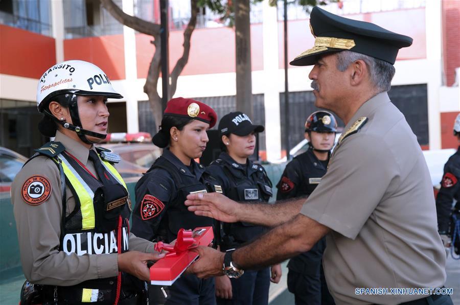 """Una policía de tránsito (i) recibe un presente durante la celebración del Día Internacional de la Mujer, en Lima, Perú, el 7 de marzo de 2017. El tema central del Día Internacional de la Mujer de 2017 de la Organización de las Naciones Unidas (ONU), que se celebrará el 8 de marzo, será """"Las mujeres en un mundo laboral en transformación: hacia un planeta 50-50 en 2030"""". (Xinhua/Norman Córdova/ANDINA)"""