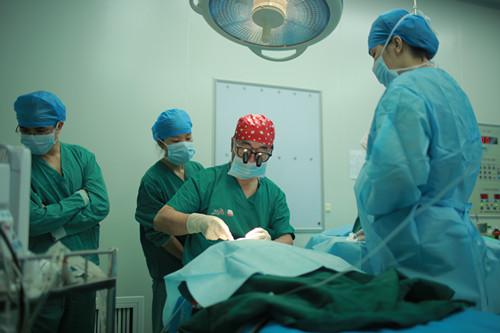 韩凯(中)为一名唇腭裂患儿进行免费手术。(资料图)
