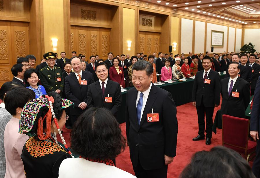 Chinese President Xi Jinping talks with female deputies when joining a panel discussion with deputies to the 12th National People