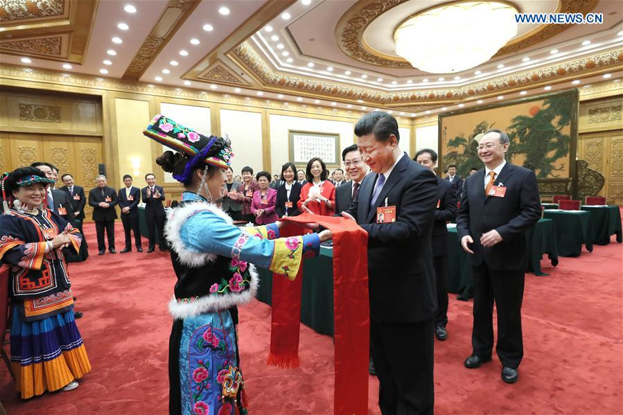 Chinese President Xi Jinping receives Qianghong, a ceremonial silk scarf regarded as a token of respect, from a deputy of Qiang ethnic group when joining a panel discussion with deputies to the 12th National People