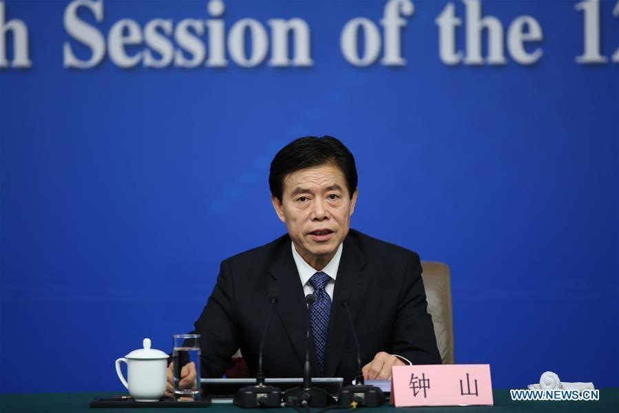 Chinese Minister of Commerce Zhong Shan answers questions at a press conference on structural adjustments and innovation for the fifth session of the 12th National People