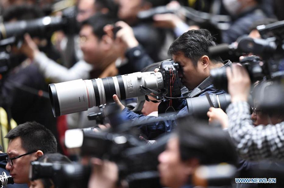 Photographers work at the closing meeting of the fifth session of the 12th National Committee of the Chinese People