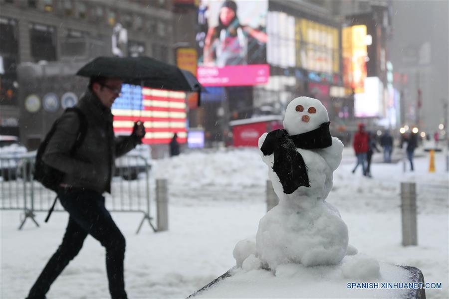 """Un hombre camina frente a un muñeco de nieve en Times Square en Nueva York, Estados Unidos de América, el 14 de marzo de 2017. La tormenta invernal """"Stella"""", a sólo una semana de la entrada de la primavera, comenzó el martes a afectar el noroeste y centro de la costa atlántica estadounidense provocando la cancelación de vuelos, el cierre de escuelas, la cancelación del servicio superficial del metro y advertencias para no circular por carretera, de acuerdo con información de la prensa local. (Xinhua/Wang Ying)"""