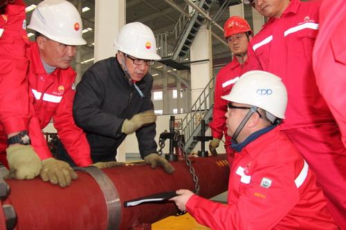 周若厅(左二)向中亚管道哈国培训人员讲解顶针式抢修卡具操作原理。