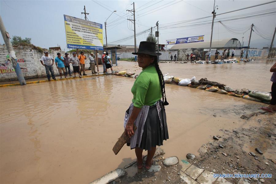 """LIMA, marzo 16, 2017 (Xinhua) -- Personas observan una calle inundada luego del desborde del río Rímac, en un sector de Huachipa, al este de Lima, Perú, el 16 de marzo de 2017. Las lluvias intensas provocadas por el Fenómeno El Niño costero afectan Lima desde el mediodía del miércoles. Las adversas condiciones climáticas, con lluvias torrenciales, siguen afectando el desarrollo de varias regiones peruanas, lo que ha obligado a las autoridades a estar en permanente """"alerta roja"""" para atender las necesidades de las poblaciones. (Xinhua/Juan Carlos Guzmán/ANDINA)"""