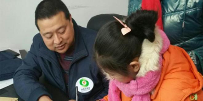 朱迎波(左)正在贫困学生家里辅导孩子写作业。图片来源:陕西省文明办
