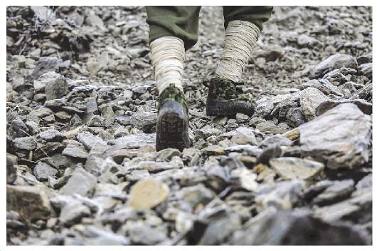 巡山队员踩着悬崖边布满碎石的小路向上攀爬,每一步都要谨慎小心。