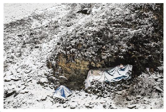 一夜大雪之后,队员们住宿的营地被白雪覆盖。这个营地是用塑料布和树枝搭建起来的棚屋,四处透风,非常寒冷。