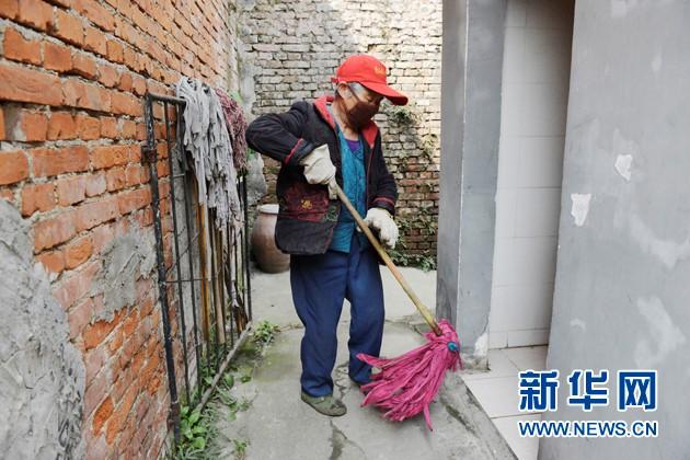 刘忠兰在清扫位于车站村的公共厕所。
