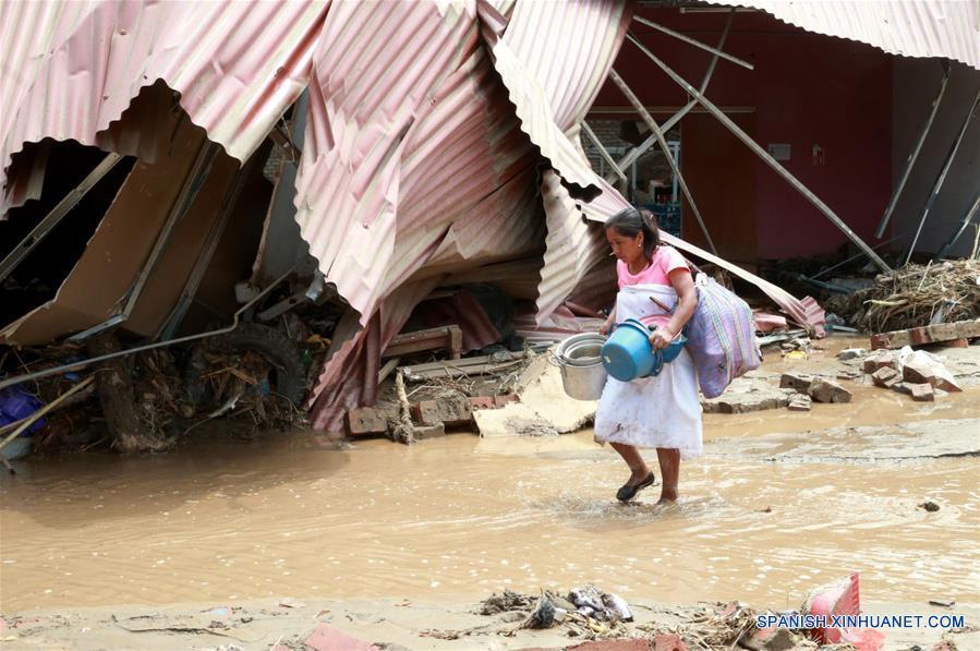 """LIMA, marzo 20, 2017 (Xinhua) -- Una mujer camina en medio de un camino inundado luego de los huaicos en Huachipa, provincia de Lima, Perú, el 20 de marzo de 2017. El Centro de Operaciones de Emergencia Nacional (COEN) de Perú confirmó que hasta el lunes 75 personas han fallecido desde diciembre pasado, 263 resultaron heridas y 30 más están desaparecidas a causa del fenómeno climático """"El Niño"""" en la zona costera. La entidad indicó en un comunicado que """"El Niño"""", que apareció débil en diciembre pasado y se agudizado en marzo, ha traído consigo 627,048 afectados en 11 regiones del país sudamericano, así como 100,169 damnificados. (Xinhua/Norman Córdova/ANDINA)"""