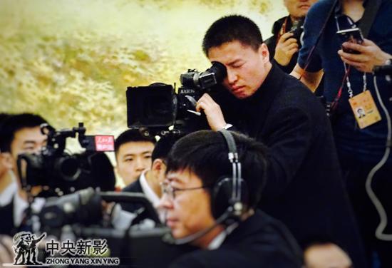 摄影师贾晓欣在总理记者招待会拍摄现场