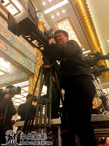 摄影师杨晓童在高台上拍摄总理记者招待会同期讲话