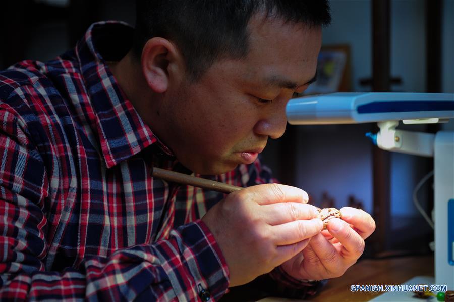 ANHUI, marzo 20, 2017 (Xinhua) -- El artista Ma Yongbing talla una figura en un hueso de durazno en Xuancheng, provincia de Anhui, en el este de China, el 20 de marzo de 2017. El los últimos 25 años, Ma Yongbing, ha creado más de un millar de piezas de esculturas en huesos de durazno. Las creaciones de Ma destacan principalmente las historias chinas tradicionales, arquitecturas, paisajes, entre otros. (Xinhua/Meng Dingbo)
