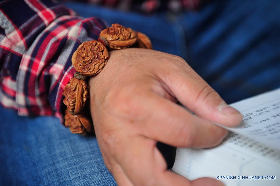 ANHUI, marzo 20, 2017 (Xinhua) -- El artista Ma Yongbing utiliza una pulsera de figuras talladas en huesos de duraznos en Xuancheng, provincia de Anhui, en el este de China, el 20 de marzo de 2017. El los últimos 25 años, Ma Yongbing, ha creado más de un millar de piezas de esculturas en huesos de durazno. Las creaciones de Ma destacan principalmente las historias chinas tradicionales, arquitecturas, paisajes, entre otros. (Xinhua/Meng Dingbo)
