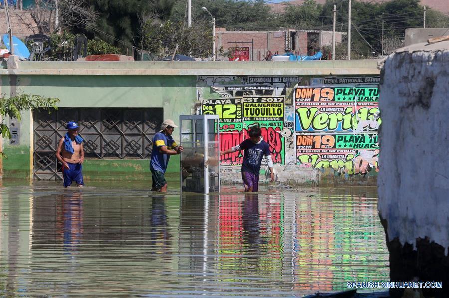 HUARMEY, marzo 22, 2017 (Xinhua) -- Personas caminan a través del agua de la inundación en la ciudad de Huarmey, en el sur de la región Ancash, Perú, el 22 de marzo de 2017. Las fuertes lluvias que se registran en Perú persistirán durante al menos dos semanas en 12 regiones del país sudamericano, informó el martes el Centro de Operaciones de Emergencia Nacional (COEN). De acuerdo con la entidad, las regiones más afectadas continuarán siendo Tumbes, Piura, Lambayeque, La Libertad y Ancash en el noroeste, Lima en el centro-este, Ica, Arequipa, Moquegua y Tacna en el sur, y Huancavelica y Ayacucho en el sureste. (Xinhua/Vidal Tarqui/ANDINA)