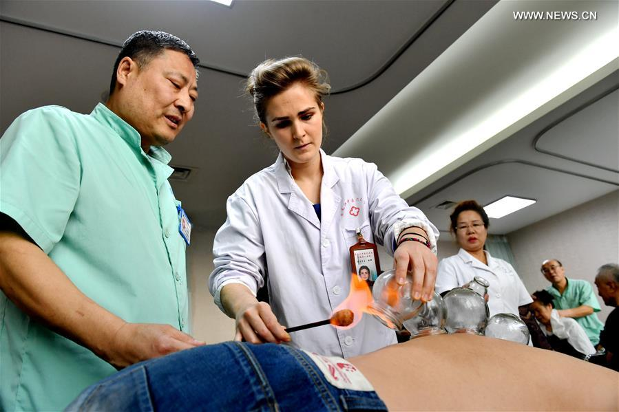 Anaelle (C), a graduate of Heilongjiang University of Chinese Medicine from France, carries out cupping therapy at the First Affiliated Hospital of Heilongjiang University of Chinese Medicine in Harbin, capital of northeast China