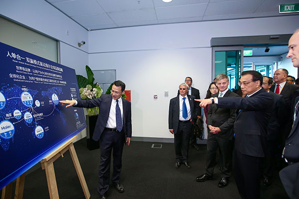 Premier Li Keqiang was accompanied by his New Zealand counterpart, Bill English, on a visit to the research center of Fisher & Paykel, a well-known local household appliance company, now majority-owned by Haier Group, a Chinese firm, in Auckland, a city in the North Island of New Zealand, on March 28.