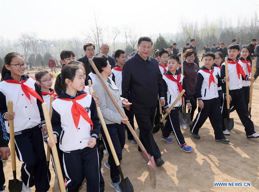 Chinese President Xi Jinping (C, front) walks with students as he attends a tree planting activity in Beijing, capital of China, March 29, 2017. China