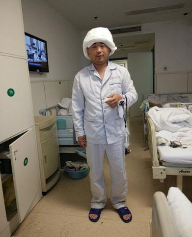 捐献头皮手术后,纪鹏飞头上缠着厚厚的纱布。