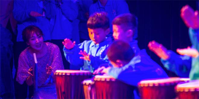在一场公益演出中,罗老师为了让自闭症孩子们能看到自己,跪在舞台上指挥他们打鼓。(来源:辽沈晚报)