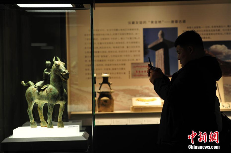 A visitor takes picture of a bronze figurine of a man riding a horse at the exhibition of antiques collected from the Ancient Tea Horse Route at Liaoning Provincial Museum in Shenyang, capital of Northeast China