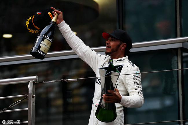 Race winner Lewis Hamilton celebrates on the podium at the Shanghai Audi International Circuit, on April 9, 2017. [Photo: VCG]