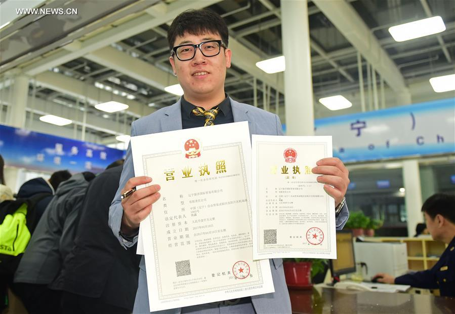 An applicant shows his business licenses at the service hall of the Shenyang area of China (Liaoning) Pilot Free Trade Zone in Shenyang, capital of northeast China