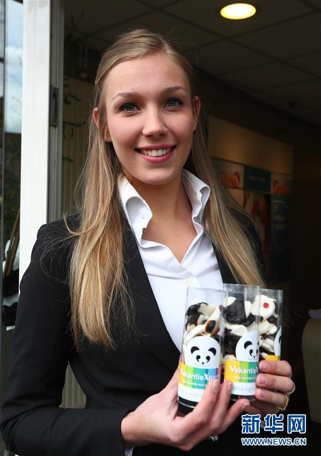4月5日,在荷兰中部小城雷嫩的一家商店,一名女子展示熊猫图案的糖果。(龚兵 摄)