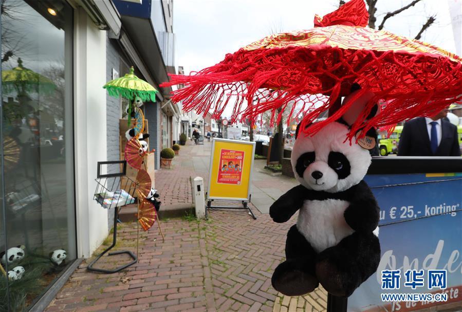 4月5日,在荷兰中部小城雷嫩,一家商店门口摆放着用于装饰的熊猫玩偶。(龚兵 摄)