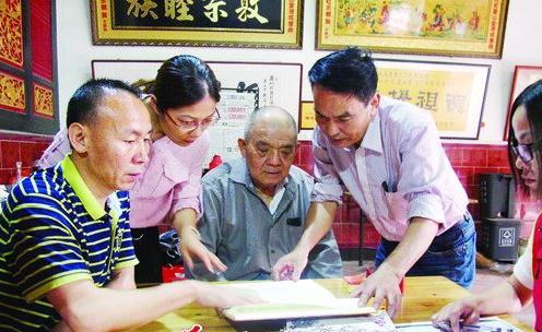 陈原来(左一)在东孚莲花社区收集探讨姓氏文化材料
