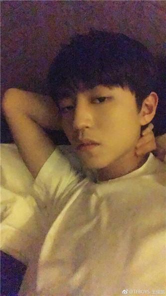照片中,王俊凯身穿白色短袖,一只手当枕头,慵懒的躺在床上,表情酷帅